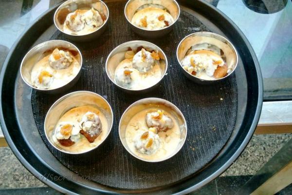 photo of gulgule / pua in rabdi ( sweet dumplings in densed condensed milk)
